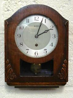 "Stained oak cased 8 day spring driven pendulum regulated kitchen clock by Bentima circa 1950, with decorative wooden moulding and visible pendulum. Silvered two tone dial with Arabic hours and matching blued steel hands. Case height - 13""."