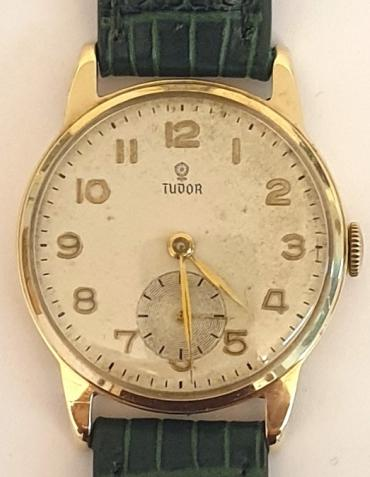 Rolex Tudor manual wind wrist watch in a 9ct gold case with dark green leather strap and gilt buckle. Silvered dial with gilt Arabic hours and polished gilt hands with a subsidiary seconds dial at 6 o/c. Signed Tudor ETA calibre 1260 15 jewel movement in a Dennison 9ct gold case with a Birmingham hallmark for 1956, model 12856 and numbered 752397.
